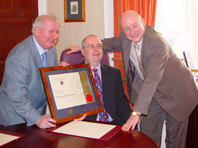 Derek Barr is congratulated by Councillor Bobby McGill and Chief Executive Dave Jones